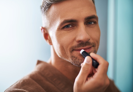 Close up portrait of attractive unshaven gentleman applying balm on lips. He is looking at camera and smiling