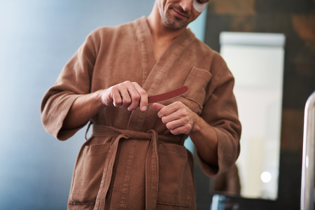 Cropped portrait of smiling gentleman in bathrobe taking care of his fingernails. Focus on male hands