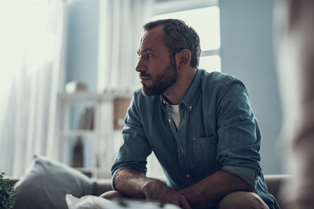 calm bearded middle aged man sitting at home and thoughtfully looking into the distance