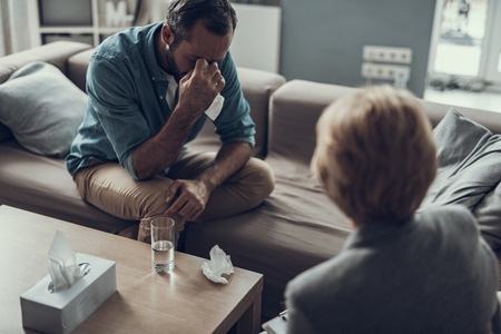 Middle aged depressed man sitting on the sofa and mopping tears from his face while having a session with his psychologist Imagens