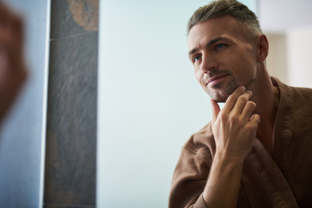 Portrait d'un beau jeune homme profitant de son reflet dans le miroir tout en touchant le menton et en souriant. Espace de copie sur le côté gauche Banque d'images