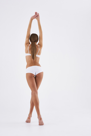 Full length back view portrait of well-shaped woman with slender legs standing on tiptoes and holding hands above her head. Isolated on white background