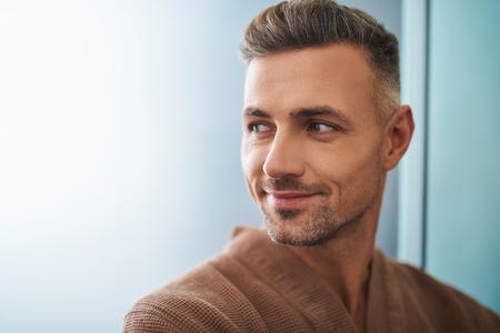Close up portrait of attractive gentleman mal rasé regardant loin et souriant légèrement. Espace de copie sur le côté gauche Banque d'images