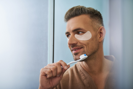 Close up portrait of handsome unshaven gentleman with masks under lower eyelids holding toothbrush with toothpaste. He looking away and smiling