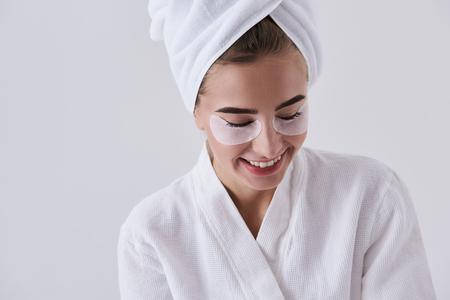 Close up portrait of beautiful smiling girl with masks on lower eyelids wearing soft bathrobe. Isolated on white background Stock Photo