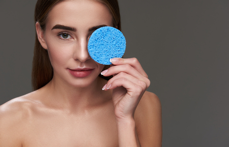 Close up portrait of attractive woman with naked shoulders holding facial cleansing sponge. She is looking at camera with slight smile
