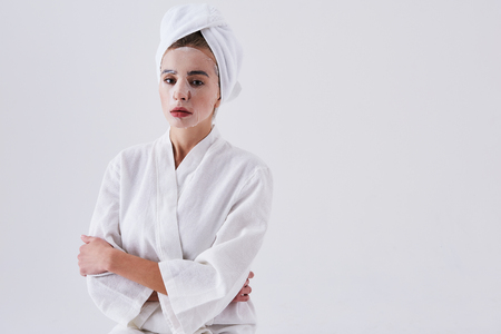 Waist up portrait of beautiful woman in bathrobe crossing arms and looking at camera with serious expression while having skin care procedure. Copy space in right side