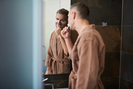 Attractive young gentleman with masks under lower eyelids looking in the mirror while cleaning teeth with toothbrush. He is wearing bathrobe
