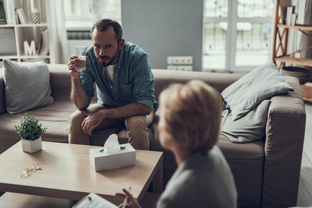 Serious bearded middle aged man holding a glass of water and looking suspiciously at the psychologist in front of him Imagens