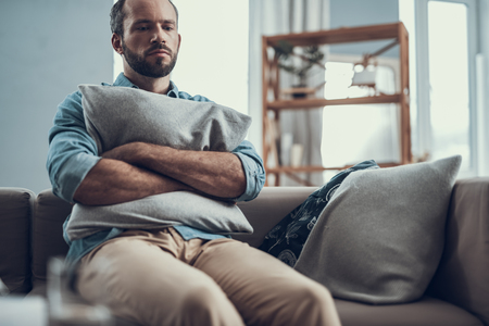 Bearded middle aged man frowning and looking depressed while sitting on the sofa and hugging a pillow