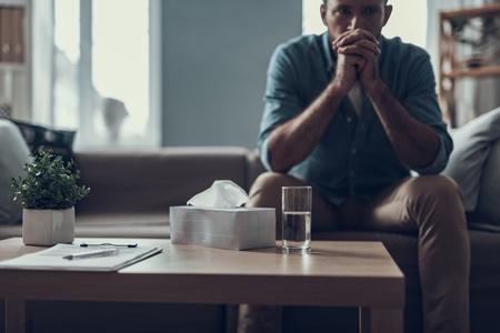 Man zit op de bank met zijn vingers gekruist voor zijn gezicht en drinkt een glas water Stockfoto