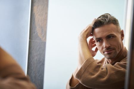 Close up portrait of attractive unshaven gentleman in bathrobe fixing his hair and smiling slightly. Copy space in left side