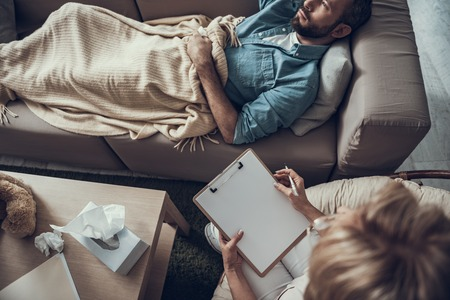 Depressed unhappy bearded man lying on the sofa under blanket and his psychotherapist sitting near with clipboard and pen