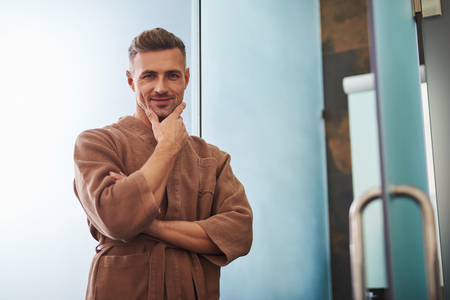 Waist up portrait of good-looking gentleman in bathrobe touching his unshaven chin. He looking at camera and smiling Stok Fotoğraf - 114993867