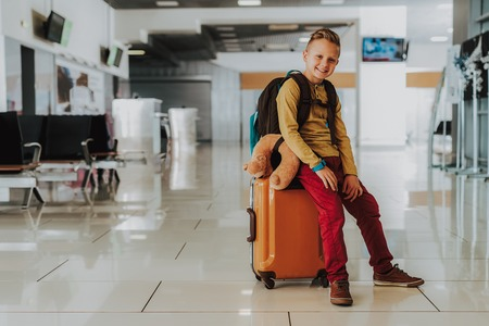 Full length portrait of merry boy sitting on suitcase in lobby.