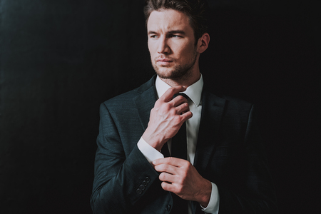 Young entrepreneur in elegant dark suit frowning and touching the cuff of his shirt while standing near the black wall and looking into the distance