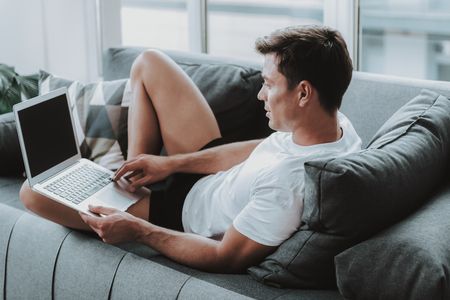 Dark haired calm man lying comfortably on the sofa with a white t-shirt and looking at the laptop on his laps Standard-Bild