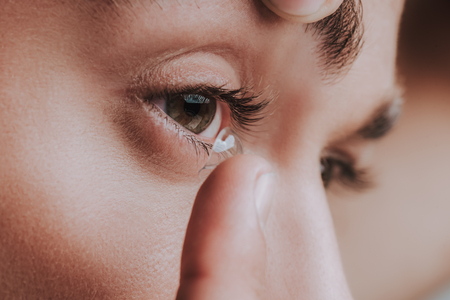Close up of the eye and person placing contact lens on the surface of it Stock Photo