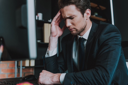 Unbearable headache. Close up of young man in elegant suit sitting at the table with his eyes closed and touching head while having sudden pain