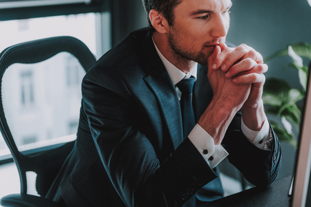 Close up of thoughtful elegant man in dark suit sitting with his hands near his face and looking calm 写真素材