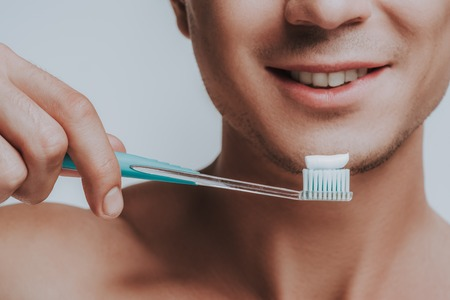 Happy young man smiling and revealing his white teeth while holding a toothbrush with toothpaste on it near the face