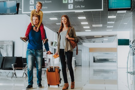 Smiling parents with son are walking with luggage at airport. Stock Photo
