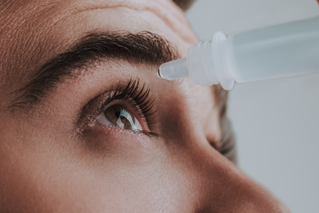 Close up of man looking up while using eye drops carefully
