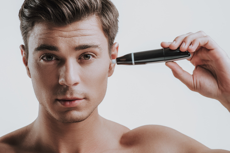Calm handsome young Caucasian man standing shirtless against the grey wall and carefully using his nose and ear hair trimmer in left ear