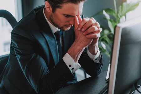 Difficult day. Young handsome businessman in elegant suit sitting at his workplace with closed eyes and touching face with thumbs while feeling tired 写真素材