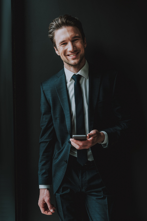 Happiness. Cheerful emotional young entrepreneur in elegant suit standing against the black Stock Photo