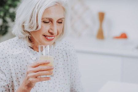 Focus on smiling elderly woman holding glass of fresh drink in kitchen. Copy space in right side