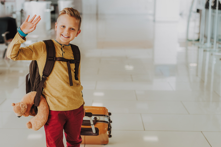 Full length portrait of smiling kid saying good-bye. He is going on holiday and carrying luggage at airport.