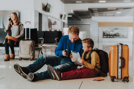 Focus on joyful father and little boy sitting on floor near suitcase and boarding documents at airport. 스톡 콘텐츠 - 115461191