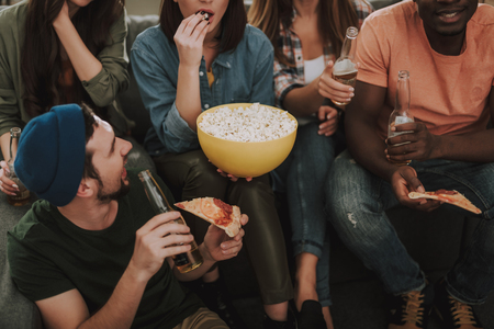 Cropped portrait of friends sitting on couch and enjoying beer, pizza and popcorn.
