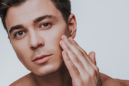 Young Caucasian man slightly touching his skin on the cheek and looking thoughtful