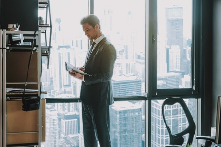 Thoughtful young businessman in elegant suit standing next to the window in his office with skyscrapers 写真素材