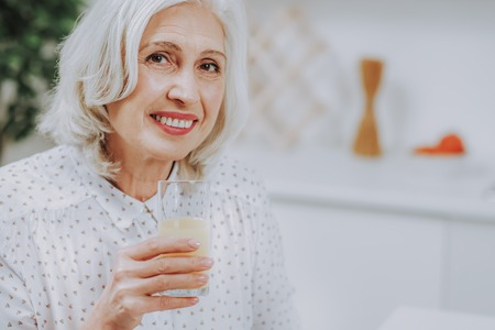 Focus on portrait joyful mature woman holding glass of juice at home. Copy space in right side