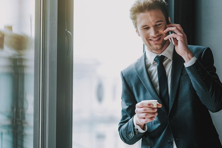 Positive handsome young entrepreneur  next to the window with a carton cup of coffee and smiling during a pleasant phone talk