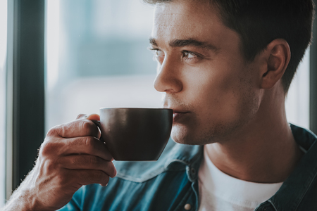 Thoughtful dark haired man looking into the distance while holding a small cup and slowly drinking his coffee 스톡 콘텐츠
