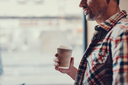 Cropped photo of mature man in checkered shirt standing in cozy cafe with copy space for text. He holding paper cup in hand and smiling Stock Photo