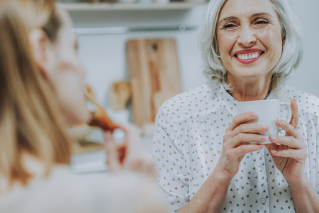 Focus on cheerful senior lady sitting at table with her daughter and looking at her with love. They are drinking mugs with morning beverages and eating tasty buns. Copy space in left side