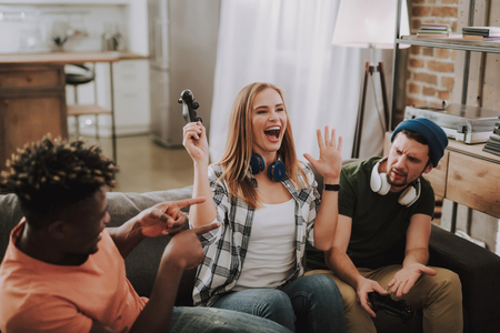 Portrait of excited young lady holding joystick and screaming with joy. Stock Photo