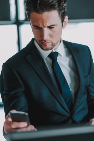 Reading messages. Concentrated young man in elegant suit with a tie sitting alone and slightly frowning while looking attentively at the screen of his modern smartphone