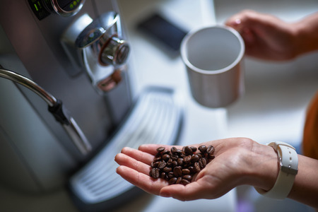 Close up of female hands holding aromatic coffee beans and mug. Girl standing near coffee machine Stock Photo