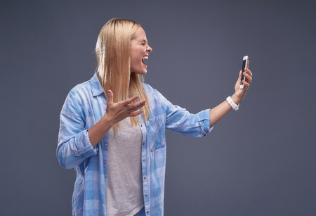 Waist up portrait of stressed young lady holding smartphone and shouting at it.