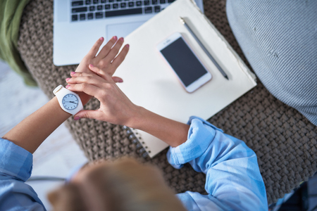 Vista superior de la niña con camisa azul tocando su reloj de pulsera. Señora sentada en el sofá con ordenador portátil, teléfono móvil, cuaderno de espiral y lápiz Foto de archivo