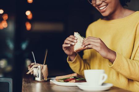 Foto recortada de mujer sonriente en jersey amarillo sentado en la cafetería. Ella come un buen sándwich para el desayuno.