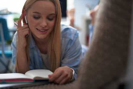 Attractive blond girl holding pencil while lying on couch with notepad. She looking down and smiling