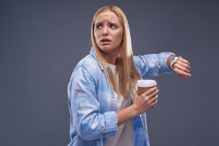Waist up portrait of attractive young lady in panic holding cup of coffee and looking away. Stok Fotoğraf - 115460514