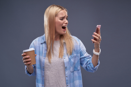 Waist up portrait of emotional blond girl holding cup of coffee and shouting at smartphone.